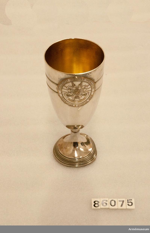 """Grupp M II. Silverpokal (försilvrad koppar?) med förgylld insida, fot med två släta kantringar och däremellan en ring dekorerad med fyra liggande ovaler. På pokalens utsida 19 och 33 mm från överkanten 5 mm breda graverade bårder i form av fyra ringar, mellan de två inre pärlstavar. Över bårderna fäst en rund silverplatta (medalj?), diameter 45-48 mm med relieftext i ring: """"Internationale Officiers Wedstrijden Herdenking v.H. 10 Jarig Bestaan"""", därinnanför två lagerkvistar ihopbundna med rosett och därovanför text: """"Tiende Wapenfest s'Gravenhage 26 Februari - 1 Maart 1907 Personelle wedstrijd degen 6 e prijs"""" (personelle, degen och 6.e graverat). På motsatt sida en annan medalj, relieftext i ring: """"KONINKLIJKE OFFICERS SCHERMBOND OPGERICHT 1. JANUARI 1897"""", därinnanför ett emblem bestående av Nederländernas av kunglig krona krönta vapensköld omgivet av en eklövs- och lagerkrans, därbakom lagada i kors två gevär med bajonetter samt 6 värjor och floretter med olika fästen, nertill textband: """"SEMPER PARATUS""""."""