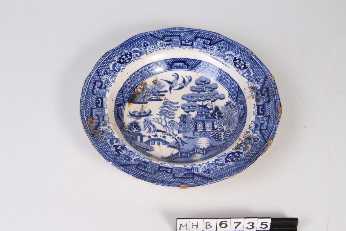 Japansk inspirert landskap, med trær, fugler, og bygninger.  Willow pattern mønster.