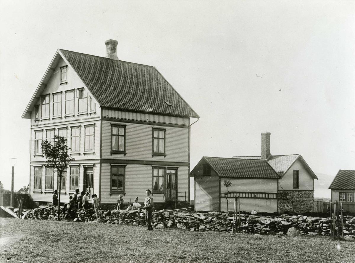 Huset er flyttet fra Visnes ca. 1896. Muret bakeribygning oppført sept.1896 av Halvor Østebø. Bendik Eileraas drev bakerforretning fra 1913. Han overtok eiendommen i 1917. Mellom uthus og hus i Strandgt. ses Karmsundet. Steingard langs Haraldsgt. med allèbeplantning. Noen personer står foran huset.
