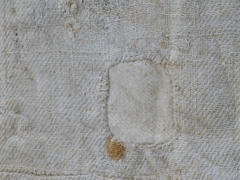Melsekk av tettvevd lerretsduk. Satt sammen av to tøystykker, håndsøm i bunnen og langsidene. Materialet er usikkert, men antakelig bomull (kanskje lin ? ) Sekken har opprinnelig hatt påsydd snor rundt sekkens åpning.  Hull i sekken er stoppet og lappet.  Påmalt initialer - som ikke er tydet.
