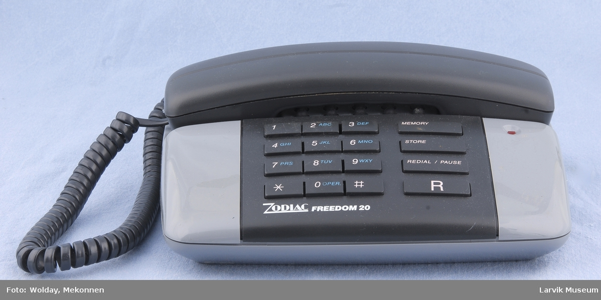 Tastafon. Tastatur på bord. Linjevalg. Funksjonsvalg. Telefon i holder øverst.