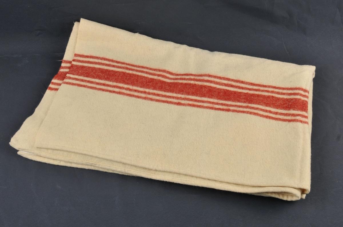 Stort tjeld av ubleika kvit vevnad. Garnet er handspunne. Bordar av fem striper i kvar ende.  Falda med handsaum.