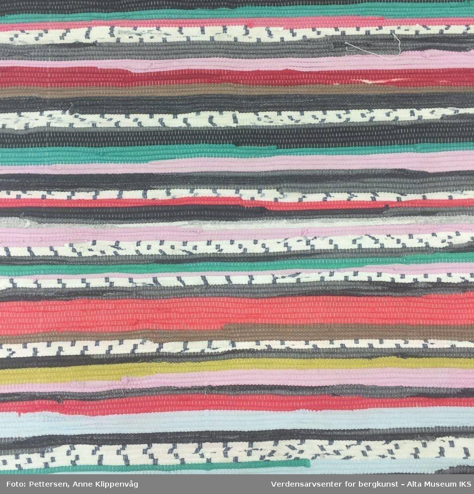 Rektangulær fillerye med ulike farger. Hvite rysjer på hver kortende.
