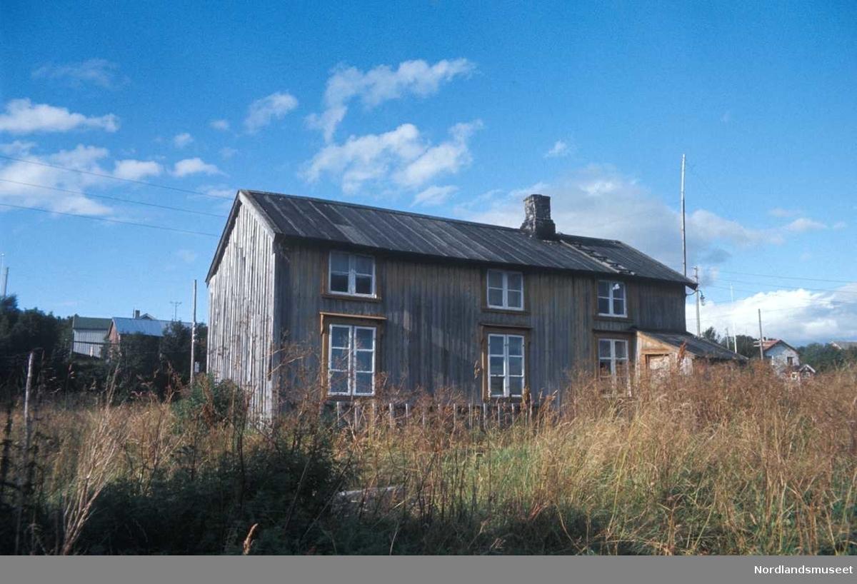 En husmannsstue fra Bertnes, Bodø, umalte vegger med stående panel, vinduene har oransje ytterrammer og hvite innerrammer og smårutet glass, huset er i to etasjer og på taket ligger det en stige, det er et utbygg på langsiden, bak sees noen flere hus og blå himmel, mens forran sees et villniss av gress.