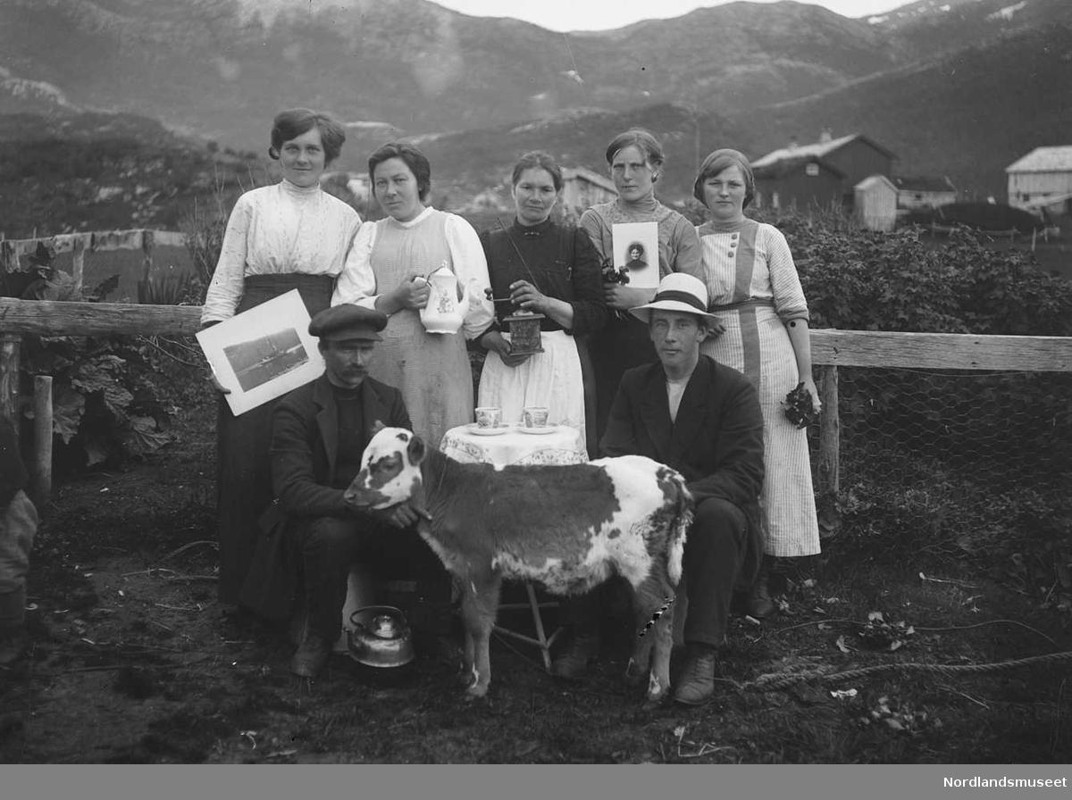 6 personer og en kalv ute. Hus. Mann med hatt og 5 kvinner, ca. 20 år. Mannen sitter ved et bord. Kvinnene står bak, kalven foran. Hus/fjell i bakgrunnen. 2 kvinner med hvert sitt bilde, landskapsbilde - portrettbilde. Kopper på bordet. Kvinne med kaffekanne.