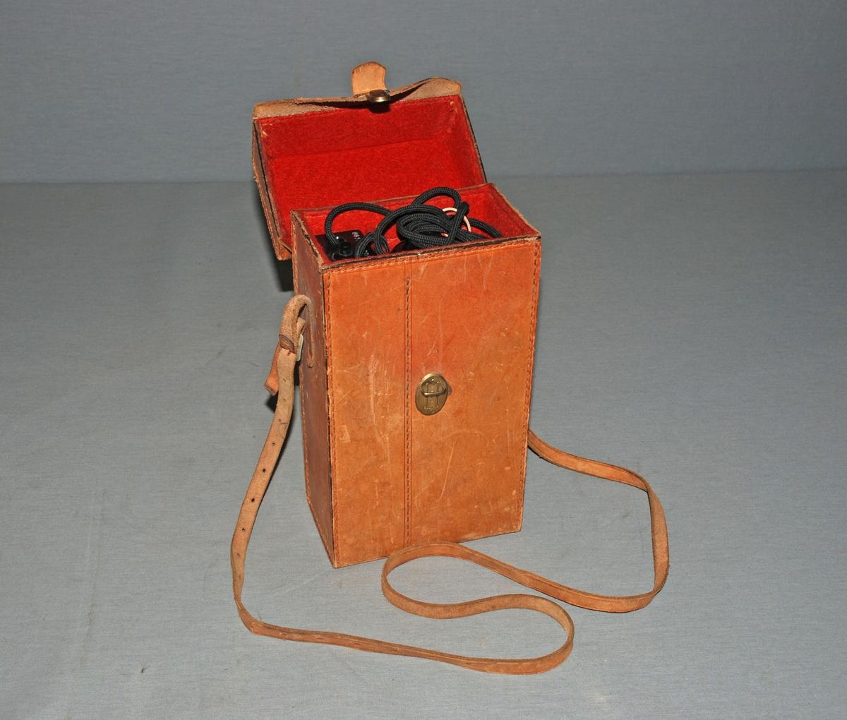 Bærbar batteridrevet telefon i veske. Telefonrør med ledning koplet til batterienhet med trykknapp på toppen og tallvalg 1-5. Montert i veskt med lukking på toppen og skulderrem. koplingsskjema på baksiden av telefonenhet.