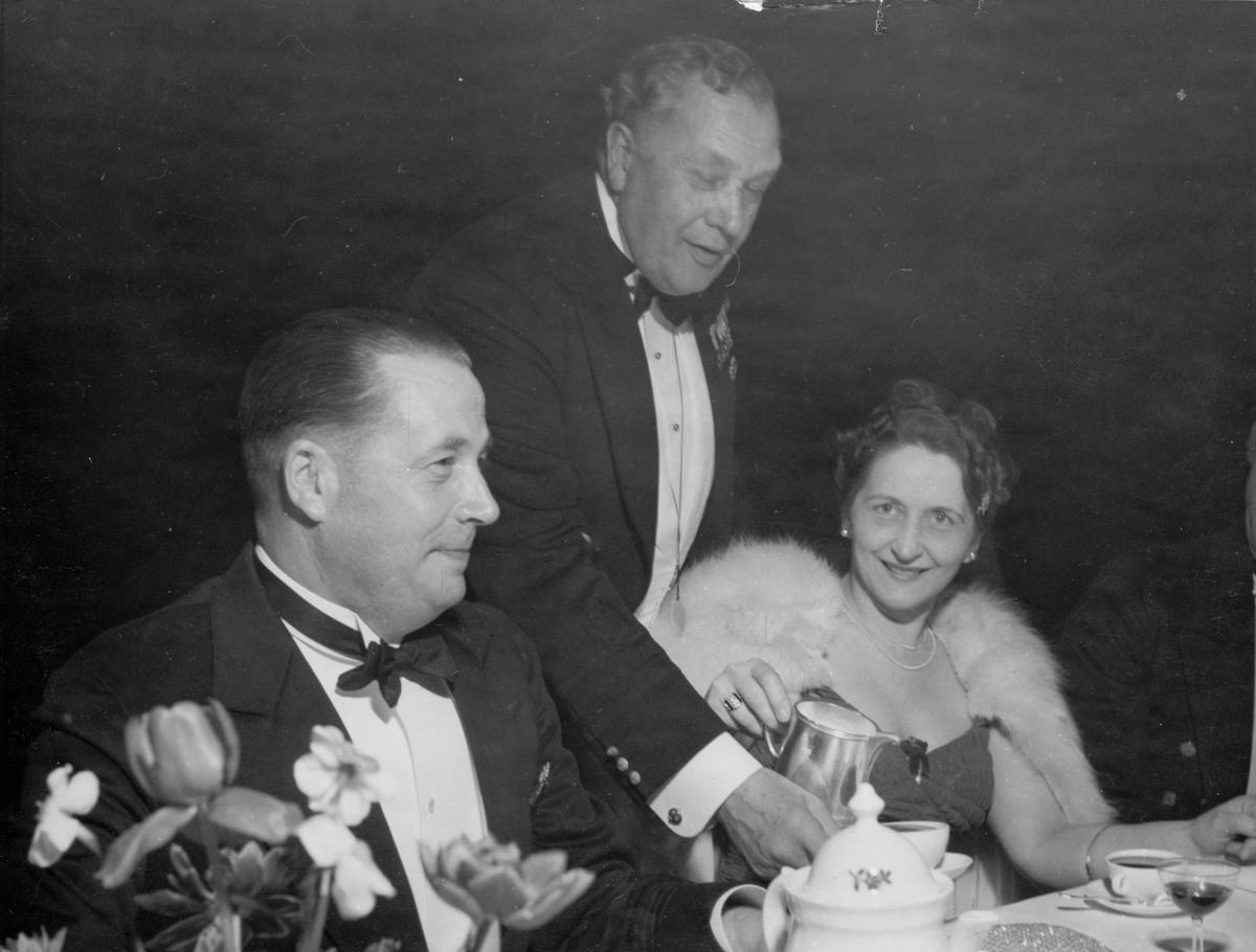 Övrigt: Från KSSS vårbal på restaurant Hasselbacken på Djurgården 8 maj 1946 (KSSS årsbok 1947 s 35). T v ses direktör Gösta Gahlnbäck; mannen som får kaffe är Charles Cahier; damen t h har inte kunnat identifieras.