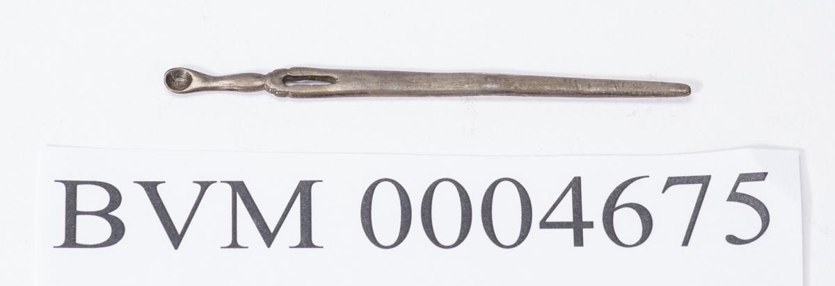 Nålelignende gjenstand trolig av sølv. Ligner litt på en stoppenål.