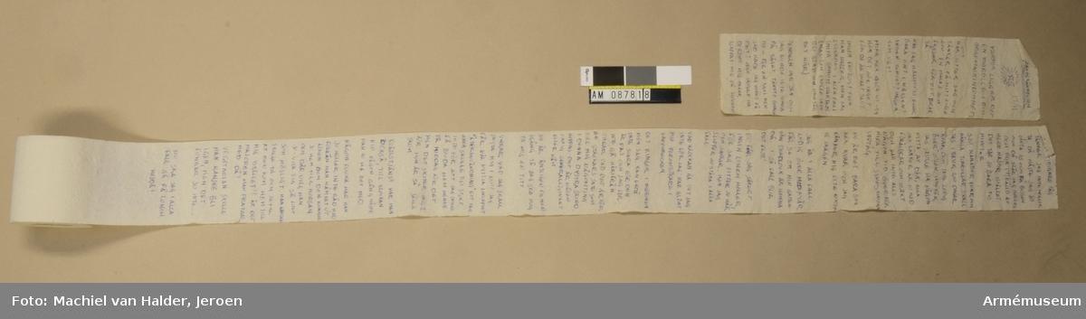 """Rulle med toalettpapper som försetts med en text i blått bläck. På sidan av rullen finns en stämpel i svart färg med texten """"STATSVERKET"""". Pappret sitter löst på rullen och vissa av perforeringarna har gått av."""
