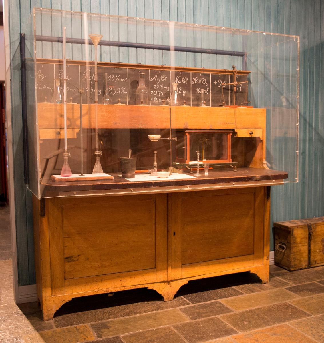 Skap med to dører nederst og bordplate i midten som kan felles ned. På toppen av skapet er en rad med ti metalknotter og en tavle langs hele toppen, mot veggen.