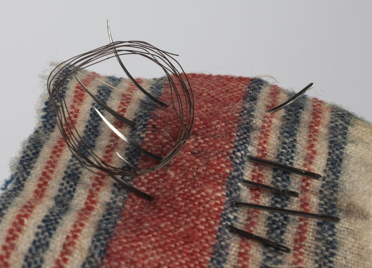 Består av en tøylapp (7x7 cm), fem krumme suturnåler og en liten rull med suturtråd av metall.
