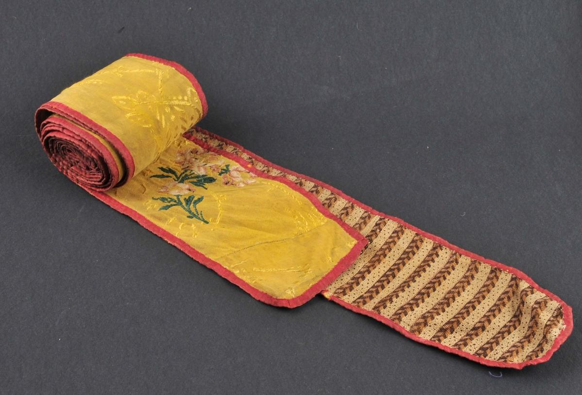 Linde med silkestoff på eine sida, lin og bomull på den andre. Det gule stoffet har blomemotiv. Bomullsstoffet er i striper. Linet er ufarga.
