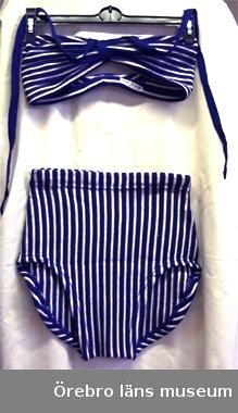 Baddräkt av helylle i trikåvävnad; smalrandig i vitt och klarblått: vita ränder i rätstickning, blå i avigstickning.1) B.H., tvärrandig; smalt bälte, hopdraget fram med enfärgat blå trikåremsa och långa, blå band, avsedda att knyta runt halsen. Bak smalnande, rundad ringning. Märkt: 44.2) Byxan långrandig; bred fåll upptill med bred resår, svängd benöppning. Prislapp med 44; 28.50.Gåva från Piscators Eftr. Manufaktur- och Klädeshandel, Rådmansgatan 28. Nora stad.I samband med städarveckan i Nora, maj 1970.