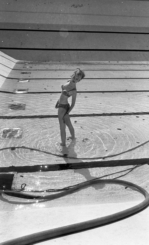 Hej Sommar, Bilskola 3 maj 1966En kvinna i bikini poserar i Gustavsviksbadets bassäng. En vattenpump syns i förgrunden till vänster.or. Han går nedför en kort trappa utomhus.