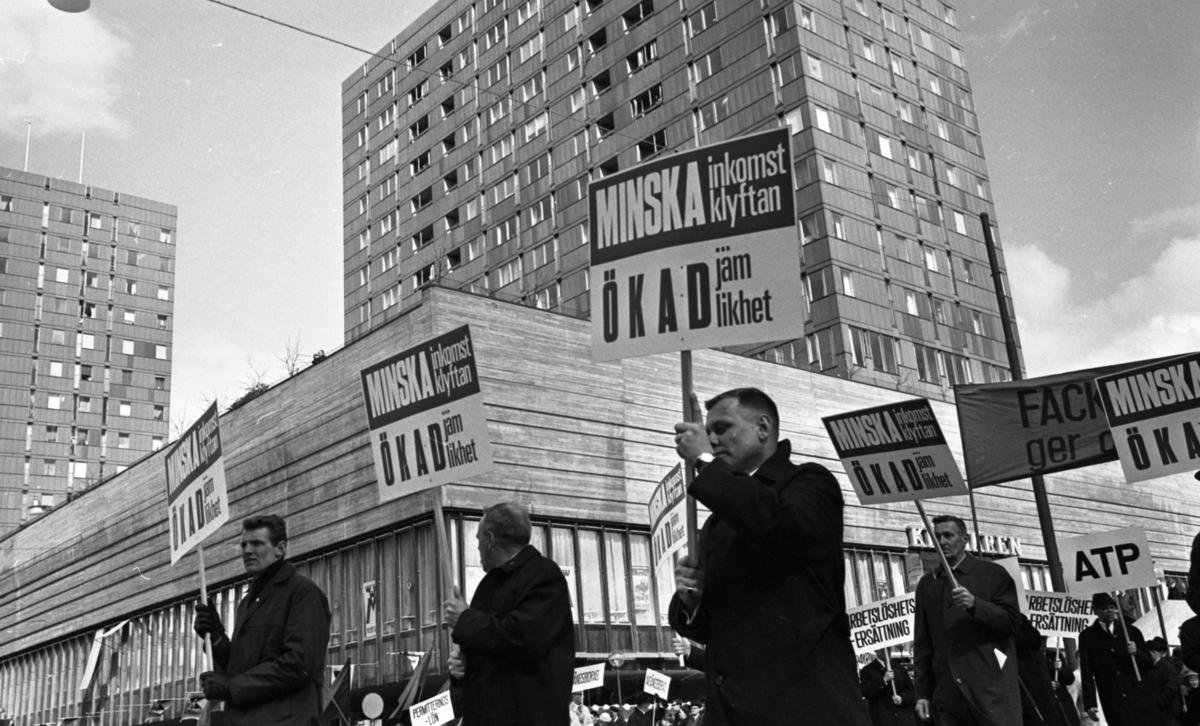 """Första maj demonstration 2 maj 1967Ett första-majtåg går genom centrala Örebro vid varuhuset Krämaren. I förgrunden syns tre män klädda i rockar och som bär på varsin demonstrationsskylt med texten: """"Minska inkomstklyftan, ökad jämlikhet."""" Publik syns i bakgrunden."""
