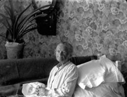 Rumsinteriör, en äldre kvinna i sängen. Clara Gustava Gusta