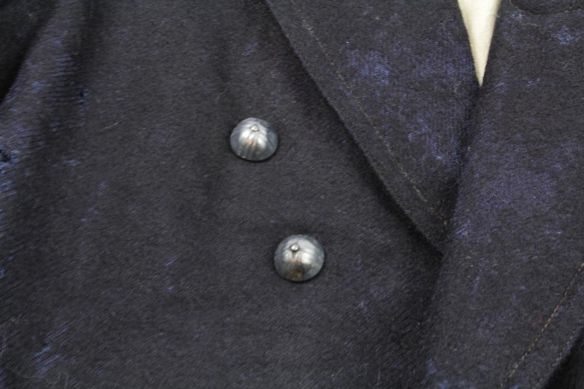 Dress i mørk blå vadmel. Maskinsydd.  a) jakke med hvitt for i ubleket grov bomull (muligens lin). Dobbel knapperad, mange av knappene mangler. To lommer nederst. To innerlommer. Hempe for oppheng sydd på innsiden av halsliningen. b) bukse, isydde knapper bak og foran for feste til buksesele. Påsydd stykke foran som åpnes ved tre messingknapper, to skjulte lommer under denne. En mindre lomme ved kanten øverst, håndsydd. Hempe bak. Hvitt for øverst i liningen.  c) vest med hvitt bakstykke. To lommer nederst. En lomme på brystet på høyre side. To knapperader, mange knapper mangler. To innerlommer. Feste for innstramming på baksiden, metallspenne.