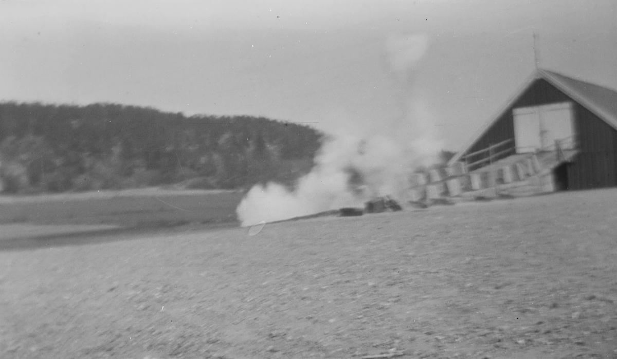 På Linderud Gård: Jorder og driftsbygning med låvebru sannsynligvis om våren. En røyksky bak lovebrua.