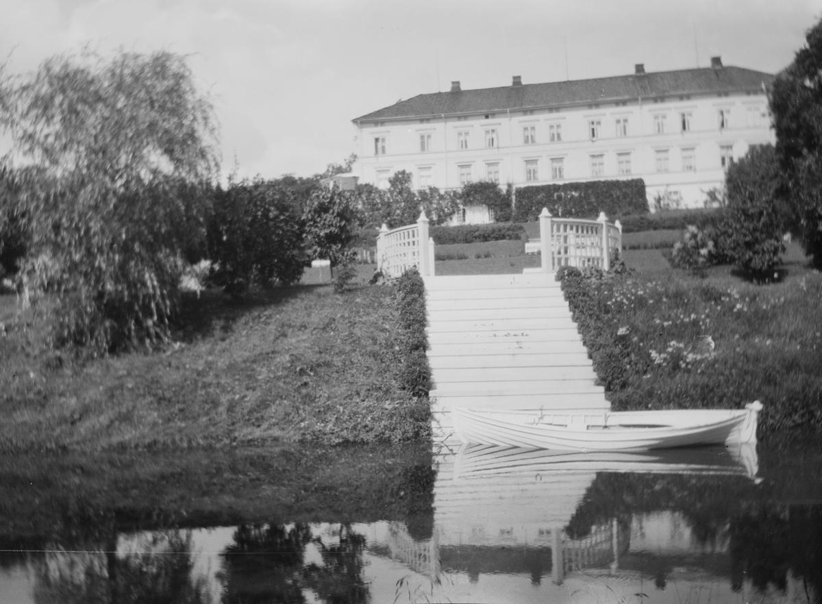 En robåt på dammen i hageanlegget på Linderud Gård, om sommeren. I bakgrunnen sees hekker, trær, trapper og avsatser med rekkverk samt hovedbygningen.