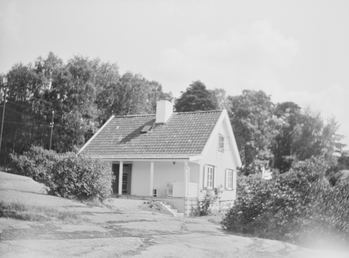 Et hus er bygget på et berg hvor det med trær og busker rundt.