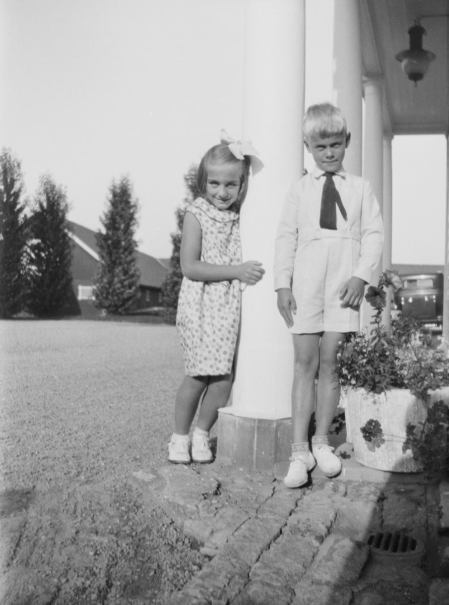 To av barnebarna til statsråd Christian Pierre Mathiesen, en gutt og en jente lener seg mot en søyle ved inngangspartiet på Linderud Gård. Pent kledd til fest om sommeren. I bakgrunnen store friserte løvtrær og driftsbygningen samt et glimt av en bil.