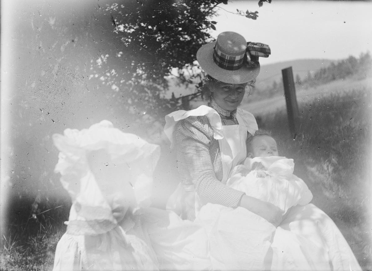 En kvinne sitter i en gressbakke sammen med to barn, et spedbarn og et litt større jentebarn kledt i blonder.