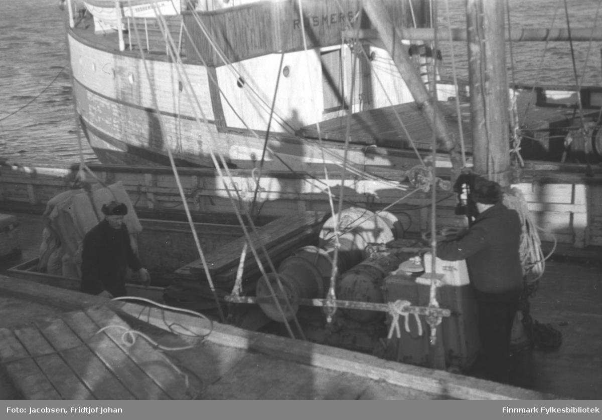Lossing av forsyninger i Hammerfest vinteren 1945-46. To menn iført mørke klær og skinnluer står på dekket. En står i lasterommet og den andre betjener vinsjen. På trekaia ligger en lasteplatt med tau. En annen fraktebåt ligger fortøyd inntil båten nærmest kamera.