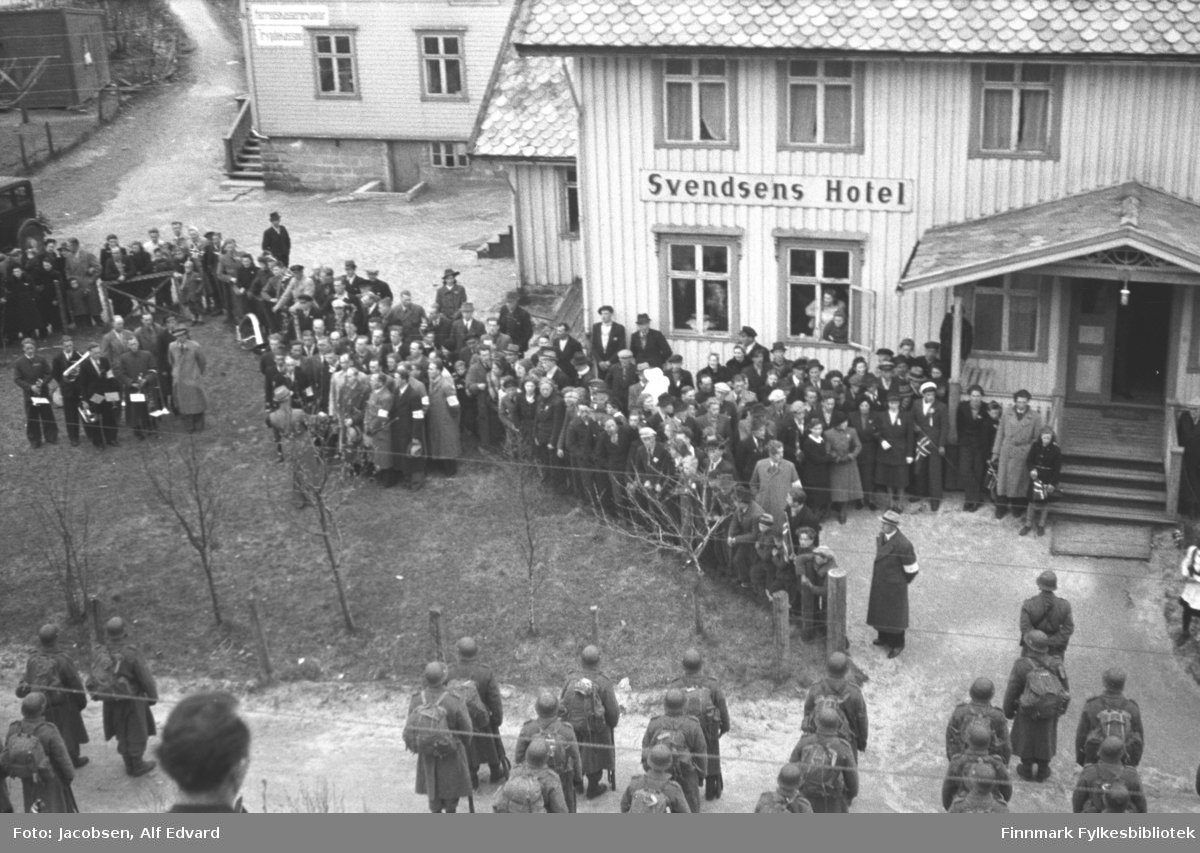 Bildet er tatt 13. mai 1945. De norske Polititropper har ankommet med båt fra Narvik og skal sikre overgivelsen av de tyske tropper. På stedet og omegn (bl.a. Nes fort, Tjeldodden fort m.fl.). De marsjerte fra Dampskipskaia med Lødingen Musikkforening foran opp til Svendsens Hotell, hvor de ble ønsket velkommen av norske militære representanter, ordfører og lensmann. Dette bildet er tatt ved hotellet. Vi ser også deler av folkemengden samt musikkforeningen.  Polititroppene er en betegnelse på den norske militære styrken som ble satt opp i Sverige under den andre verdenskrig, fra 1943 til 1945, med tanke på å gjøre tjeneste i Norge ved krigens slutt.  De ble satt inn i Finnmark høsten 1944 som del av gjenerobringen og sikringen av landsdelen. De fleste av troppene ble fraktet over grensen til Norge etter 8. mai 1945 og ble satt inn flere steder i landet for å sikre freden, passe på tyske styrker og samtidig beskytte og hindre nordmenn mot å utnytte en spent og usikker fred.  Polititroppene besto av to enheter; Rikspolitiet, som fikk politiutdannelse og Reservepolitiet. Det var den siste enheten som fikk militær utdannelse og ble satt opp og trenet som en militær avdeling.