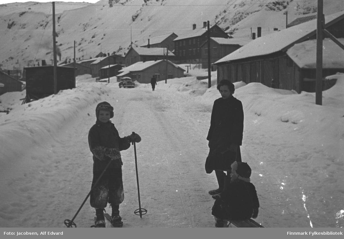En vinterdag på Molla. Til høyre på bildet står Aase Jacobsen. Hun har mørke klær, kåpe, lue, votter og sko på seg. Hun bærer en mørk veske i høyre hånd og holder tauet til en kjelke i venstre. På kjelken sitter sønnen Arne Jacobsen. Han har en mørk vinterdress og skinnlue med fòr på seg. En gutt står ved siden av dem. Han har mørke vinterklær, strikkevotter med mønster og en lue på hodet. Gutten har ski på beina og skistaver i hendene. Lenger opp i gata kommer en person gående. En bil står parket utenfor et lavt, ganske lyst hus. En del hus er kommet opp etter tyskernes brenning. Husene er i varierende form og størrelse, men gjennomgående lave. Noen større bygg står ved foten av Mollafjell, som ses bakerst på området, muligens leilighetsbygg. El-stolper står over hele området og ledninger ses spent mellom en del av dem. Det er en del snø i terrenget og brøytekanter ses langs veien.