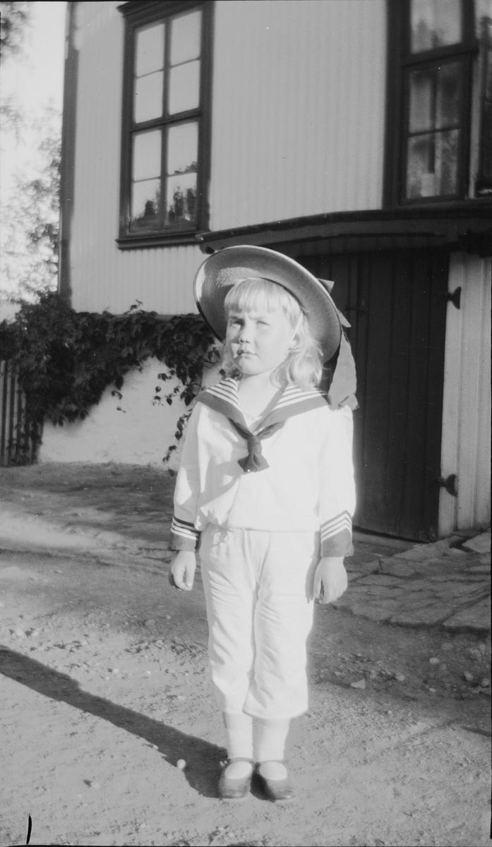 Iacob står på gårdsplassen utenfor et hus.