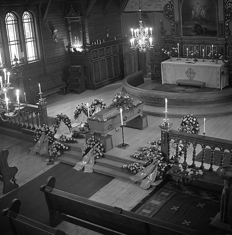 Begravning i Ljusnarsbergs kyrka, interiör av kyrkan, likkista och begravningskransar.Wickman, Kopparberg.