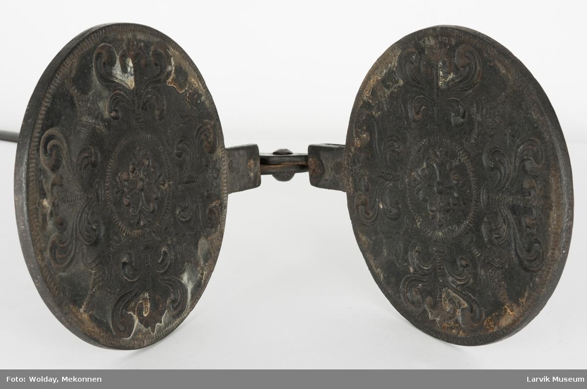 Form: rundt jern med symmetrisk blomsterornamentikk. midde armer, naglet til jernet. holdes sammen av en bøyle