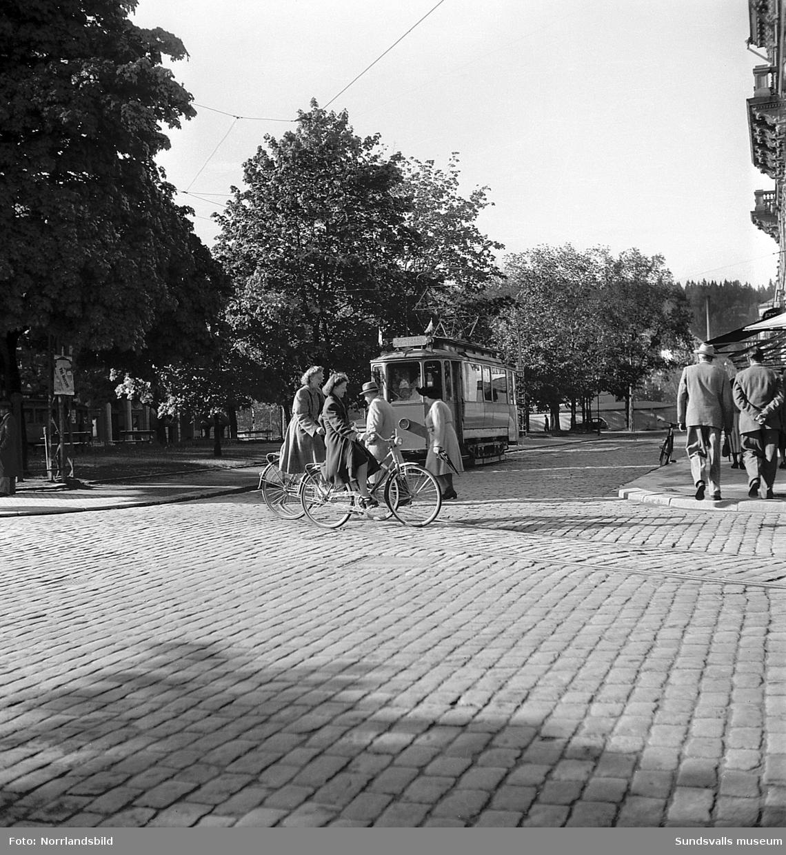 Cyklister och flanerande människor på Esplanaden, vid korsningen Storgatan, och bakom närmar sig spårvagnen på väg mot Kubikenborg.