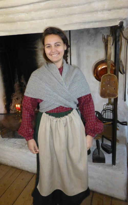 Eventyrfortelleren med sjal og forkle ved peisen i gamlekjøkkenet på Huseby.
