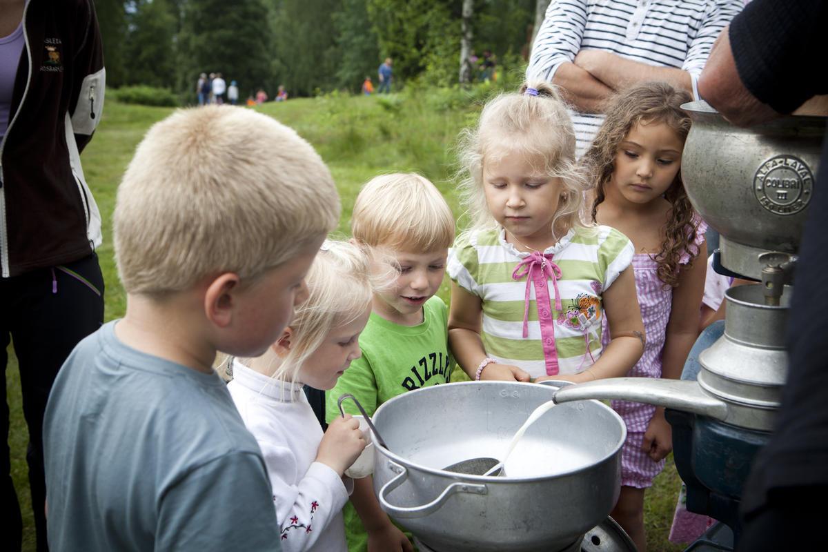 Flere barn som står rundt et melkeseparator og ser på hvordan melk separeres (Foto/Photo)