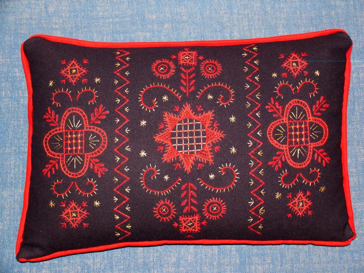 Kudde broderad med röd ullgarn och guldtråd på mörkblå yllrtyg (kläde) monterad med röd paspoal i sömmen helblå baksida ' innerkudde i fjäder.