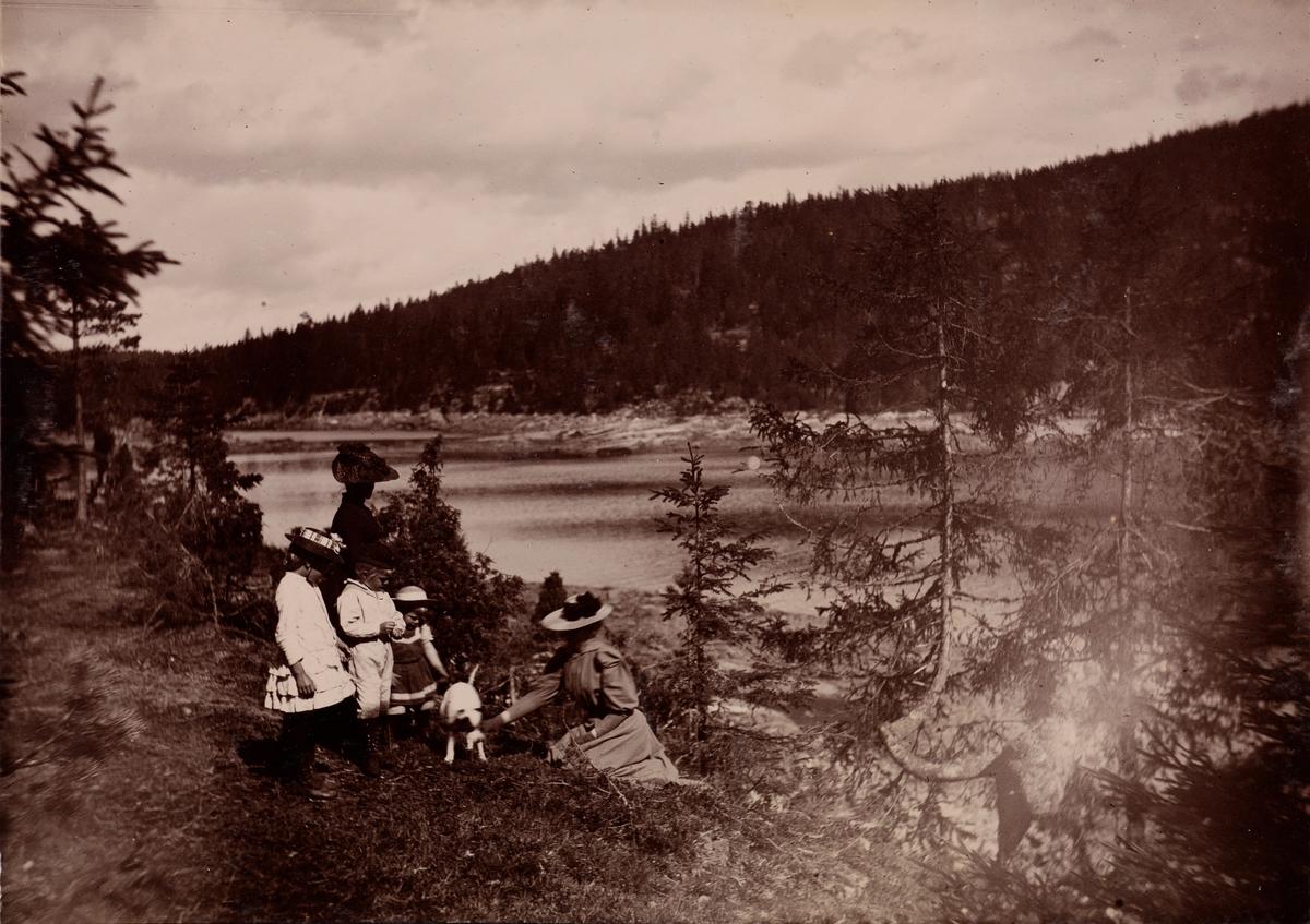 """Eva Christensen med barna Eva og Haaken Christensen og Tinken Kiær Mathiesen, og tante Akka - Agnes Mathiesen med en liten hund (Netle?) på """"Stensbruvandet""""."""