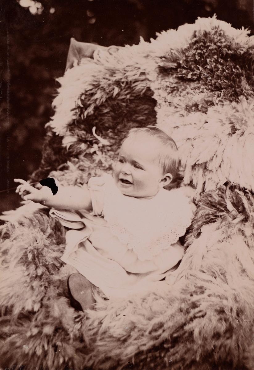 En baby (trolig Erica Mathiesen) sitter på et saueskinn i en stol i hagen og peker på noe.