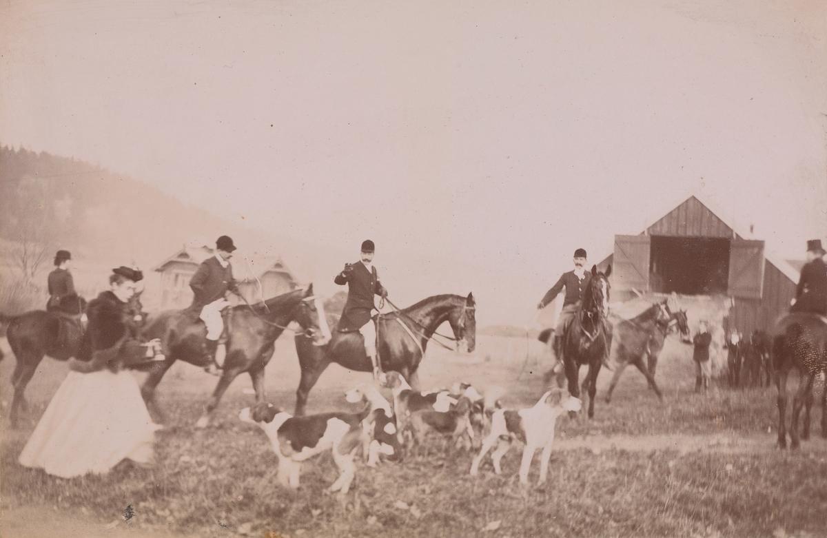Jaktritt, både mannlige og kvinnelige ryttere på deres hester og hunder på gårdsplassen på Linderud.