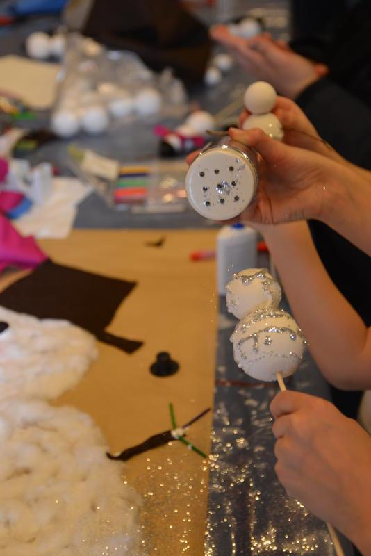 Barn lager snømenn og julegaver med glitter og isopor