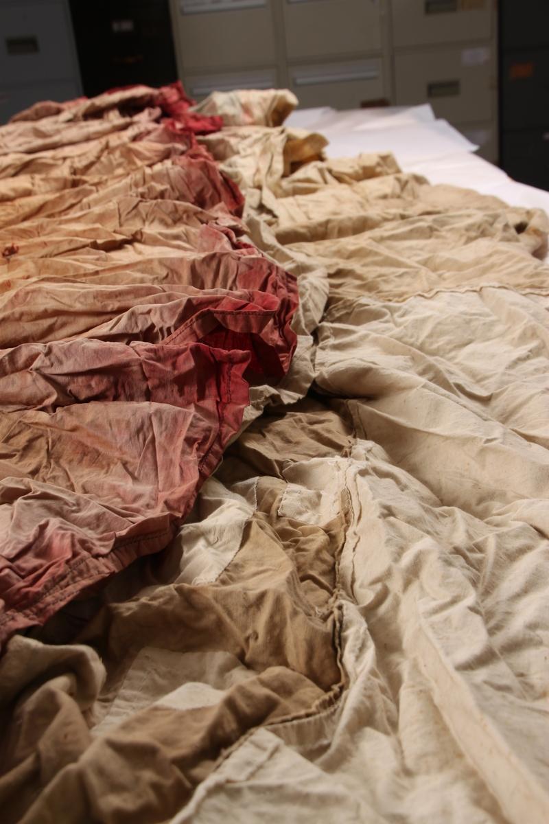 """Telt spent over en 12-kantet bunnflate med en """"hale"""" og sekke-dør. Selve teltet er laget av en enkeltduk, og er kledt med en tynnere stoffduk.  Den ytre duken er laget av et bomullsstoff svøpt rundt og festet til teltet på ulike punkter. Tøyet var opprinnelig køiegardiner for ekspedisjonsmedlemmene som ble sydd sammen med symaskin, og noen steder for hånd. Duken er sydd fast til teltet langs sømforsterkningene rundt teltets åpningsluke. Sømforsterkningene består av trolig linbånd, som er sydd over sømmene i teltet. Duken er også festet til teltet ved 12 bardunfester, dvs. metallringer, som er sydd fast på utsiden av teltduken langs teltets «midjekant» i de sømforsterkningene som går fra bunn til toppen. Ellers henger den ytre duken løst over teltet. Opprinnelig var den ytre stoffduken i en dyp rød farge, mens selve teltet var farget blått på Framheim.  I toppen av teltet er det et hull med en lærring. Dette hullet var til teltstolpen som sto i midten av teltet. Ut av lær-ringen går det tre taufester, alle i treslått hampetau. I disse løkkene er det festet barduner. Omtrent 25 cm fra toppen av teltet, er det fire «glipper» i den ytre stoffduken. Disse fungerer som lufteluker. Under den ytre duken ligger det skinnlapper som sørger for at duken ikke legger seg over luftehullene.  Selve teltet virker å bestå av to typer bomullsstoff. Veggene består av et tettere vevd bomullstøy som et vindstoff. Amundsen kaller dette dunlerret. Teltets bunn er av et tykkere bomullsstoff. Alle hovedsømmene langsmed teltets vegger er forsterket med et linbånd som går bra bunnen av teltet til toppen av teltet. Også rundt teltåpningen, som er formet som en tunnel/ sekk, er det sømforsterkninger. Tunnellen vil trolig henge ned foran inngangen når teltet er oppslått. I tunnelen er det festet fire tau gjennom hovedsømmene i teltåpningen. Muligens var disse til å snurpe åpningen igjen eller holde den åpen. Bunnen av teltet består trolig av tre lange tekstilstykker. Bunnen har 12 kanter med hull"""