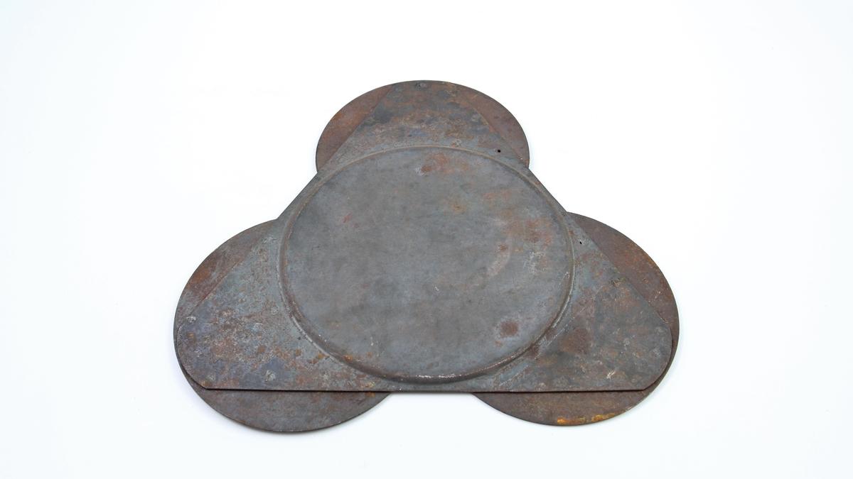 Lampemodell i metall. En trekantet plate med sirkulære plater i hvert hjørne. Trekantplatens hjørner er avrundet i flukt med sirklene. Sirkelformet avtrykk på trekantens bakside.