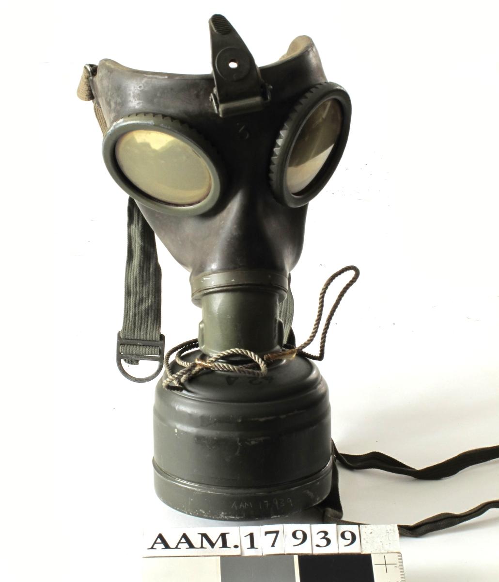 Gassmaske, tysk, fra krigen 1940-45. Sylinder av   jernblikk,  malt  mørk grønngrå.   Rifllet beholder med flatt lokk, i bunnen  ligger gassmasken, over denne en beholder,  malt med sort : byd Fe, Fe 424, tyske våpen og WA. A.533.