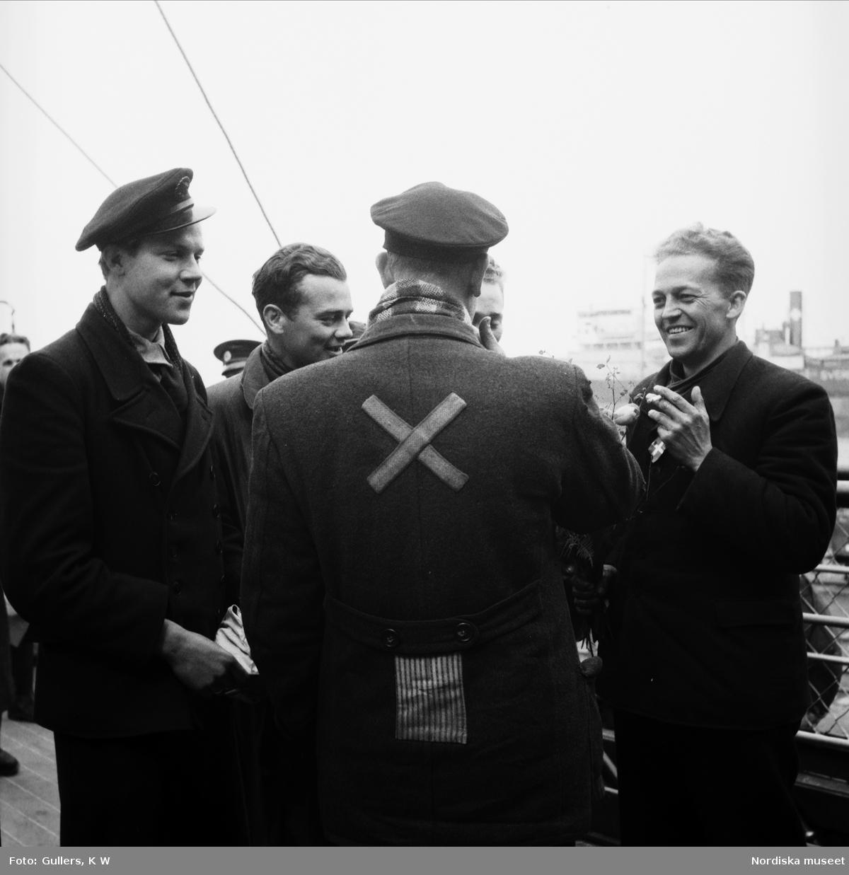 De vita bussarna. Fyra befriade koncentrationslägerfångar samtalar på färjan mellan Danmark och Sverige.