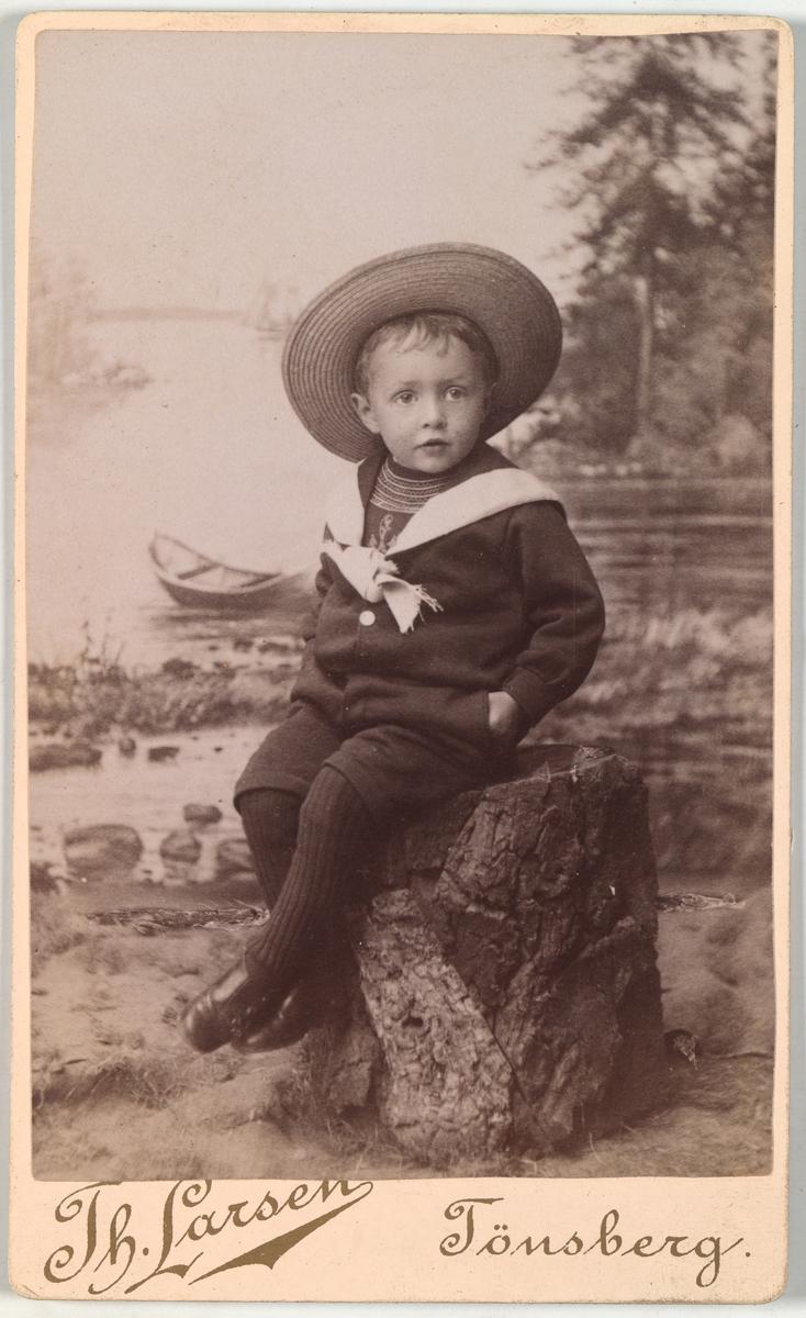 Portrett av ukjent barn matrosdress sittende på en stubbe foran en bildevegg.