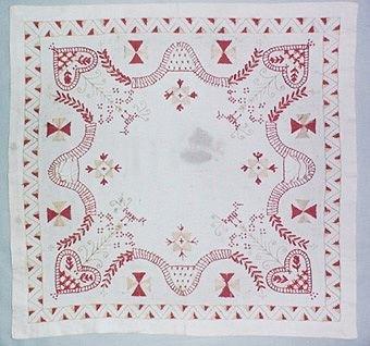 Fyrkantig broderad duk i Hallandssöm. Broderad på halvblekt linne med rött och gröngult bomullsgarn. Duken är rikt mönstrad med mönsterformer som hjärtan, fåglar, stjärnor och en broderad bård runtom.