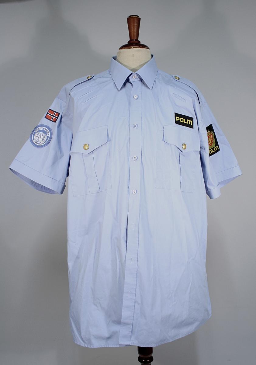 Lyseblå kortermet uniformsskjorte med politimerking etter 1995-reglementet. Norsk flagg og FN-merket høyre skulder. To brystlommer med klaff og løveknapper. Skulderklaffer uten distinksjoner.