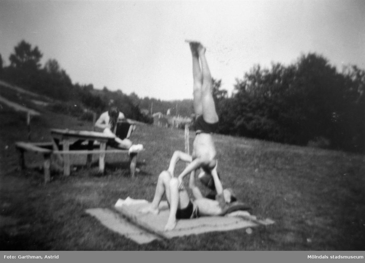 Tre män i solen (eventuellt vid sjön Lygnern) 1930- 40-tal.  En av dem står på händer på man som ligger på rygg med uppböjda knän. Okända.