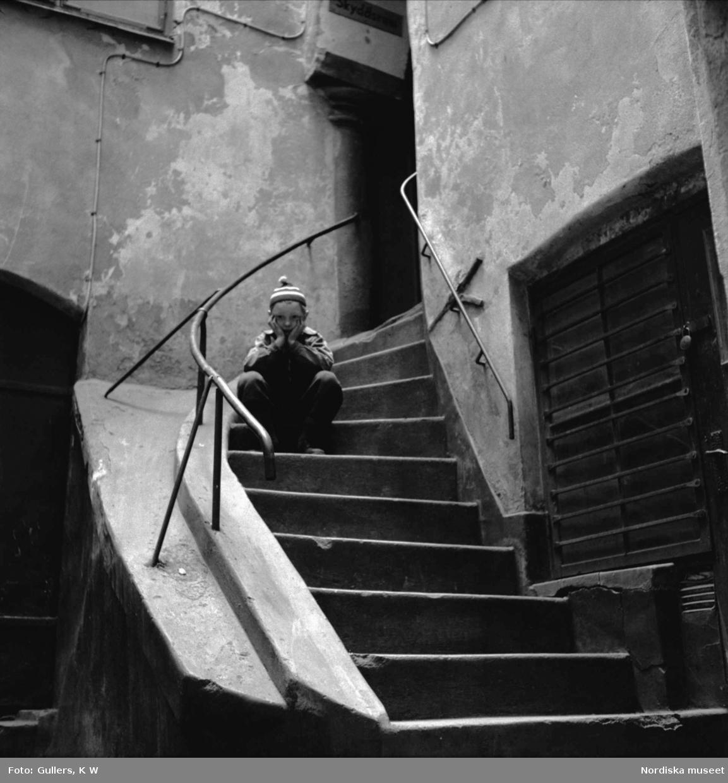 Pojke sitter på en smal trappa som bildar en genomgång mellan två hus vid Österlånggatan, Stockholm.