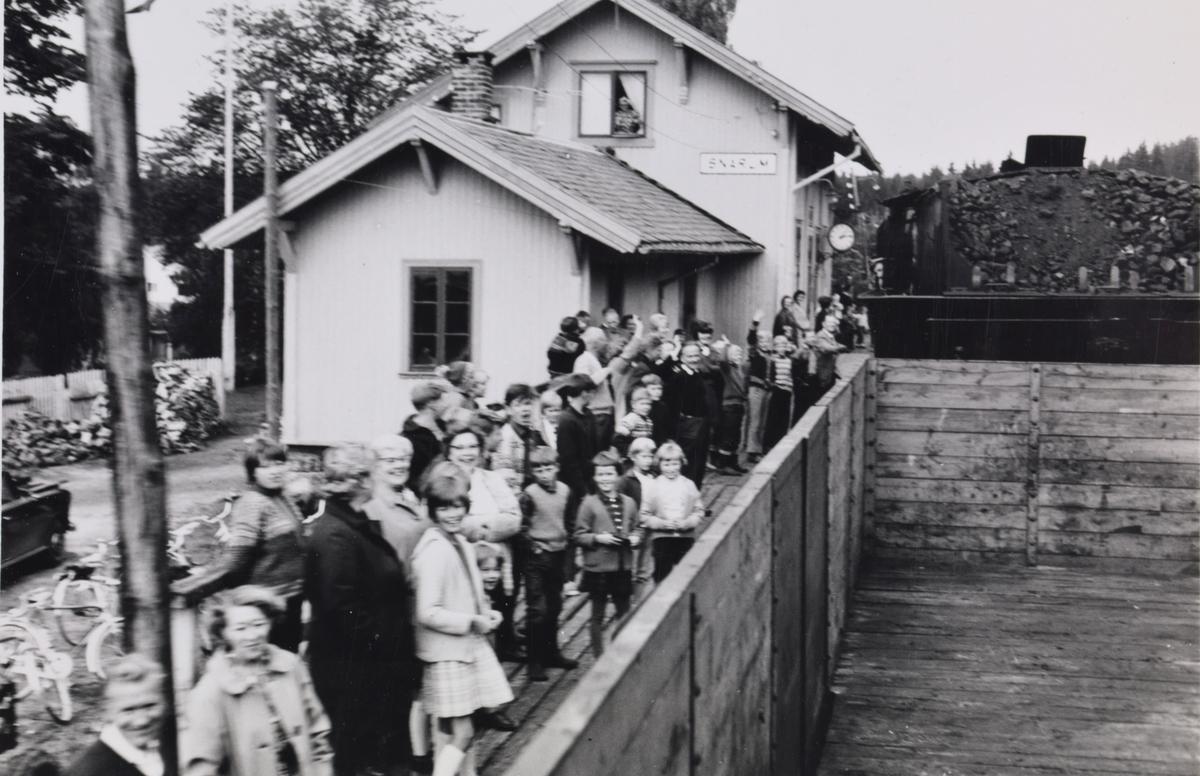A/L Hølandsbanens veterantog til Krøderen har ankommet Snarum stasjon. Toget trekkes av damplokomotiv 18c 245. Lokalbefolkningen har møtt opp for å hilse toget velkommen.
